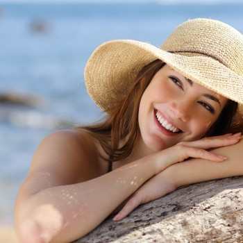 A woman with a healthy smile lounges on the beach