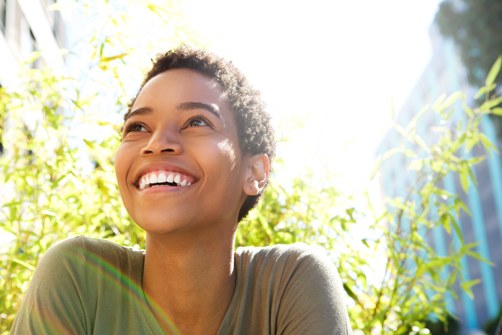 A young woman in nature looking up and smiling