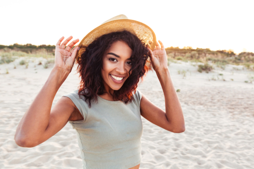 A young woman on the beach holding her hat and smiling